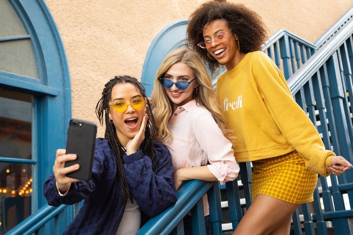 group of teenagers smiling at a cell phone