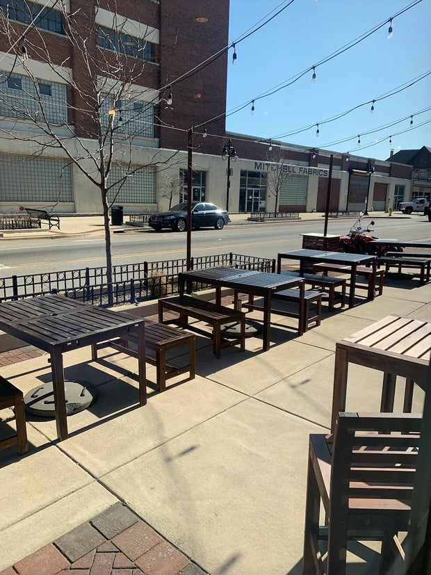 Wooden tables and chairs on sidewalk with string lights (Zion 2)