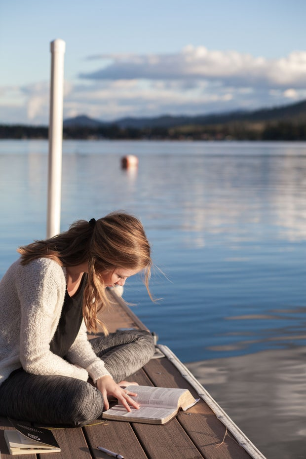 woman reading book on dock