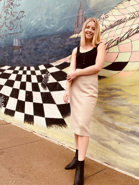 girl in midi skirt in front of checkered mural