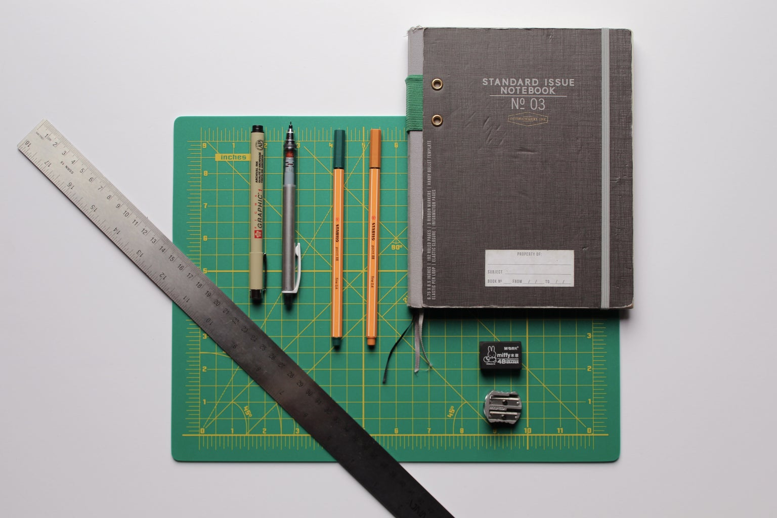 black covered book with pencils