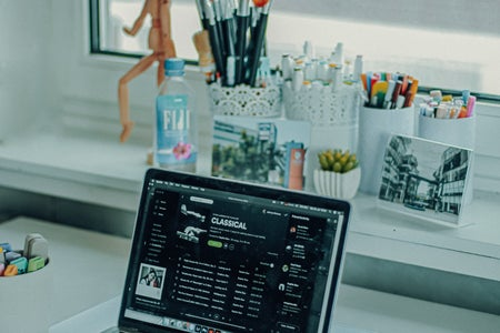 laptop screen displaying Spotify playlist at a desk.