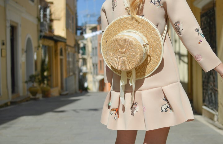 woman with pink coat and straw hat