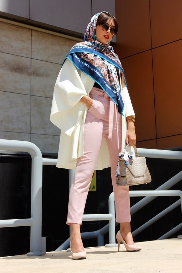 A woman wearing pink pants, a white blazer, and a printed scarf