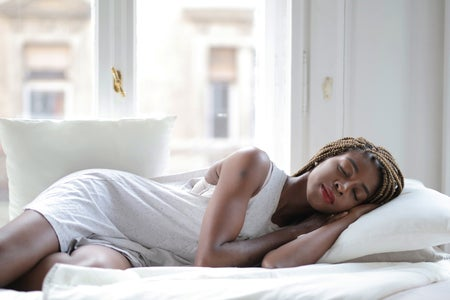 Woman in white shirt sleeping in bed