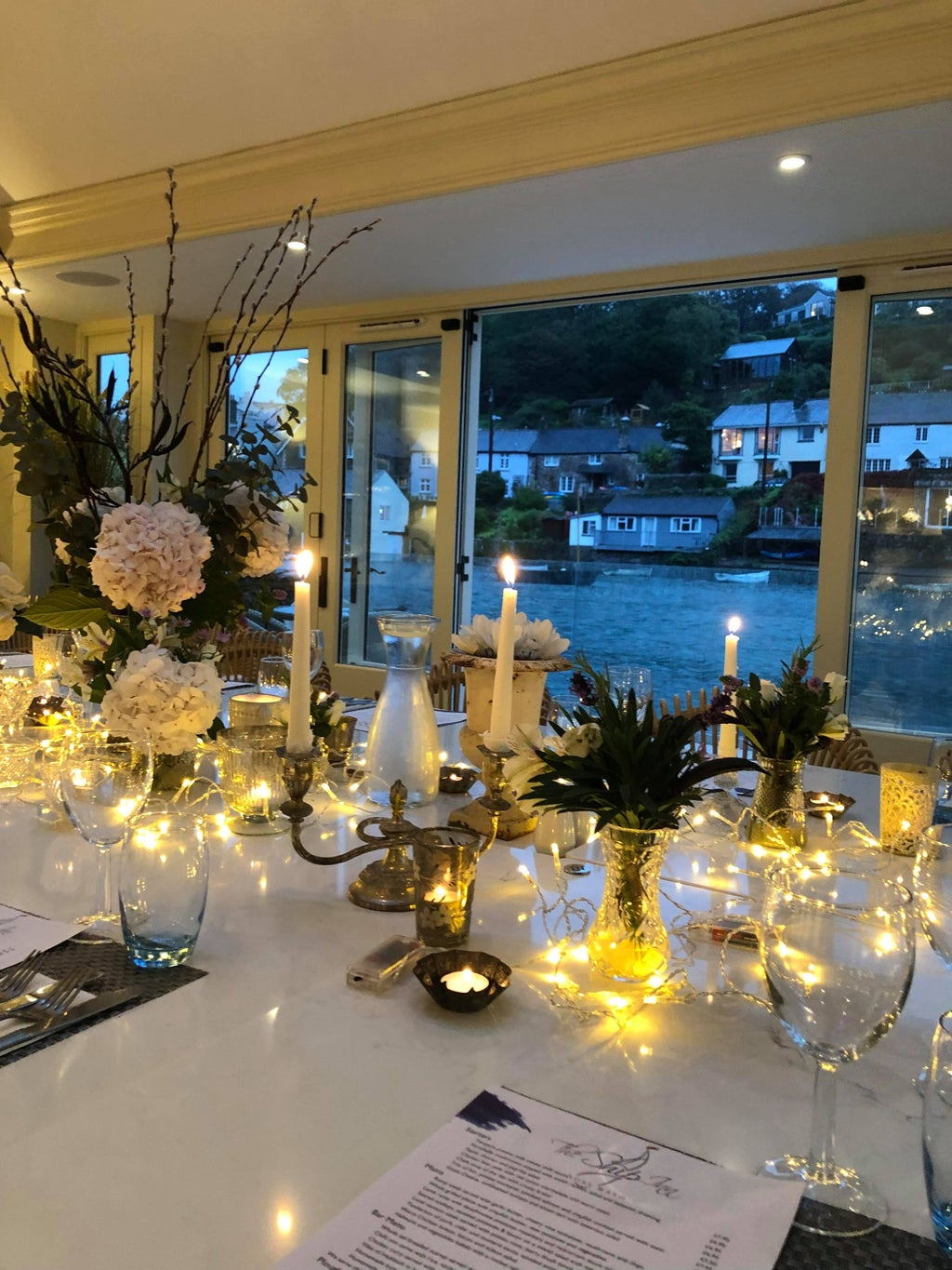 A restaurant conservatory with candles, cutlery and decorations