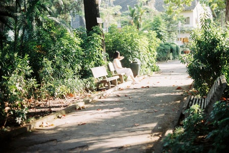 woman in a white dress sitting on a bench near a street