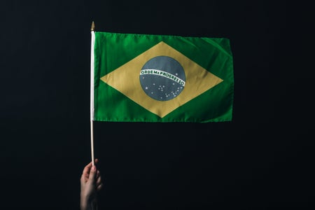 Brazilian flag being held by a hand against a black back drop