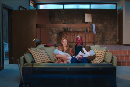 Wanda and Vision holding babies in front of a TV in Wandavision
