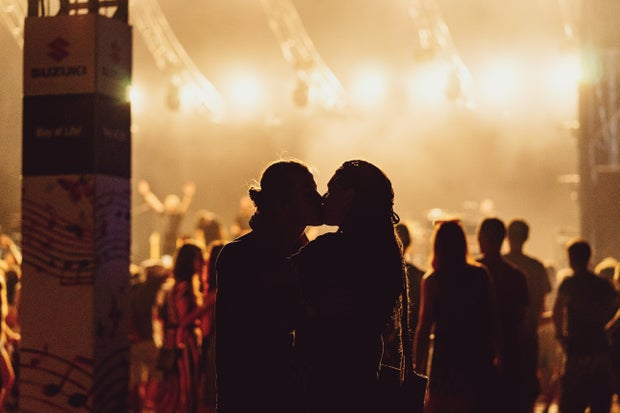 Two people kissing at concert