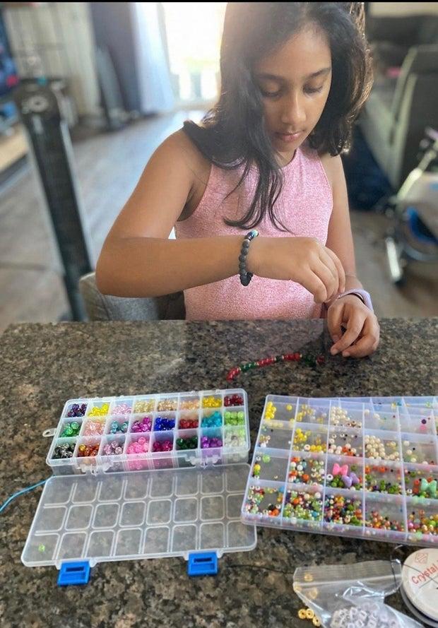 Little girl making a bracelet