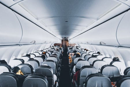 The inside of a plane. Many seats are packed closely together.