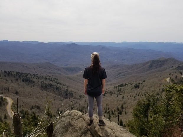 standing on cliff with mountains in view