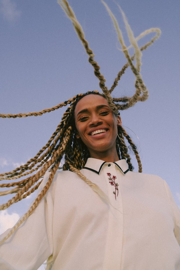 black woman with long blond braids smiling outside