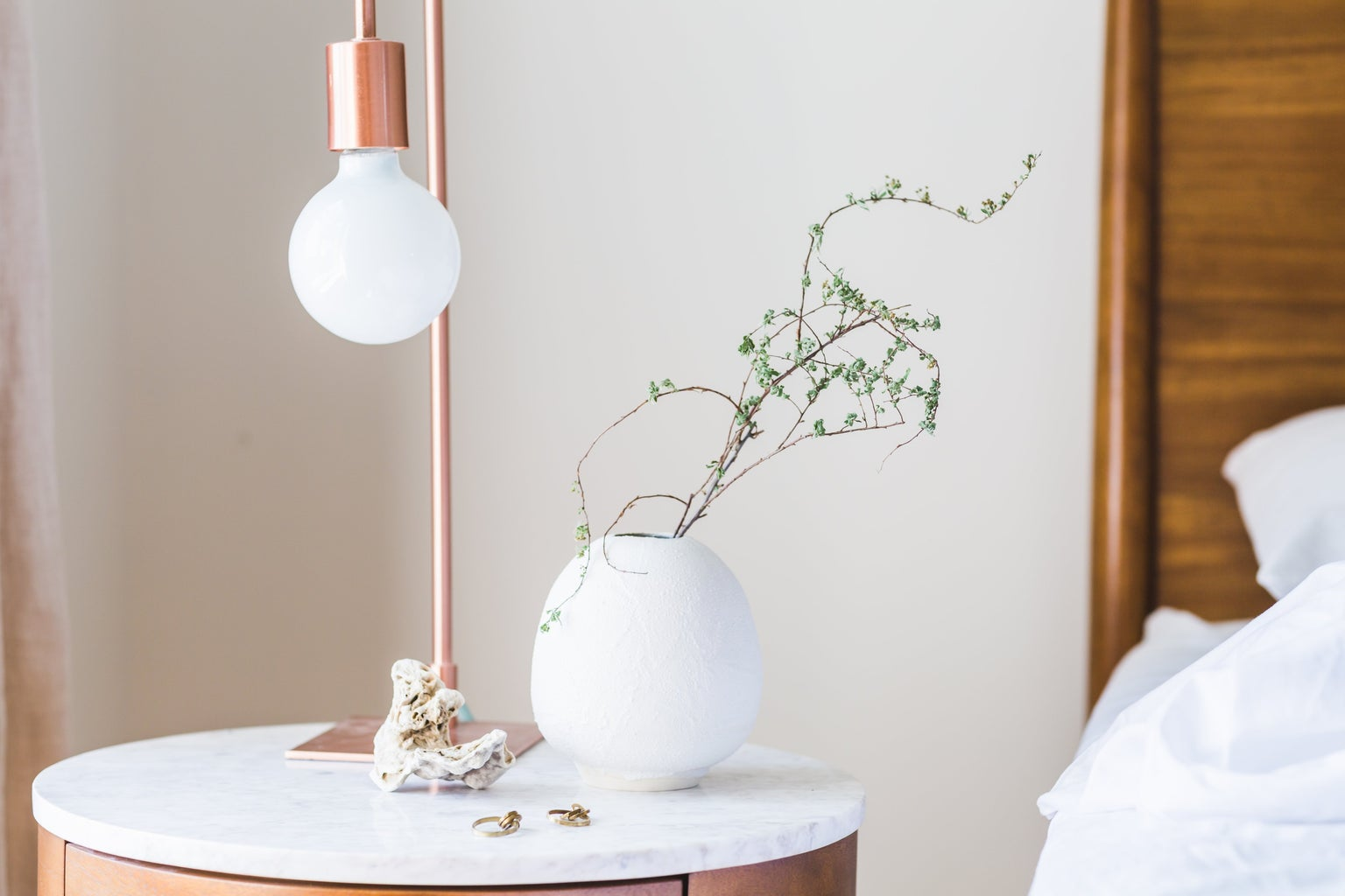 white and rose gold bedside table lamp next to bed with plant