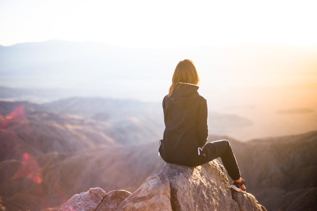 Person sits on rock before a mountain at sunrise.