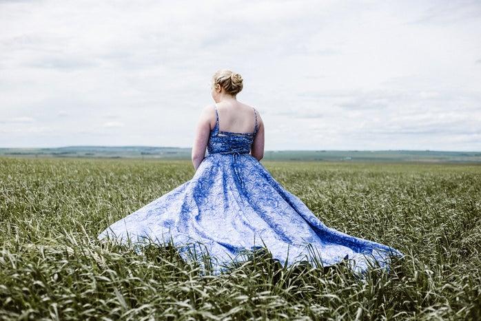 woman standing in long dress on green grass field
