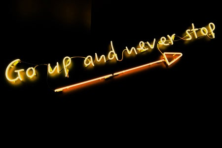 """neon quote saying """"go up and never stop"""" on a black background with an arrow underneath the words"""