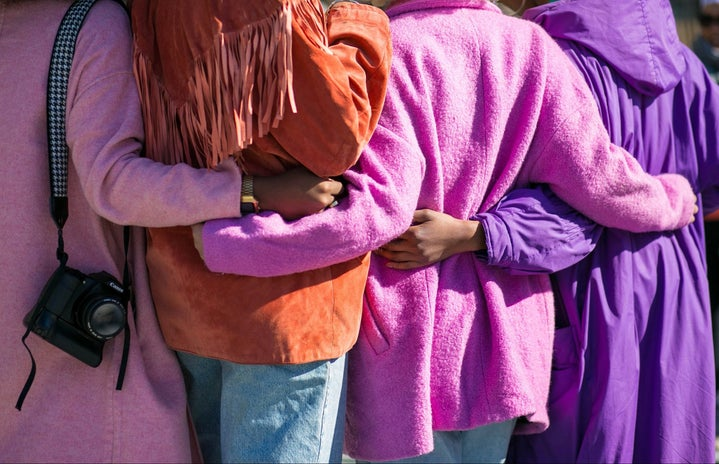 Four people holding each other in shades of purple