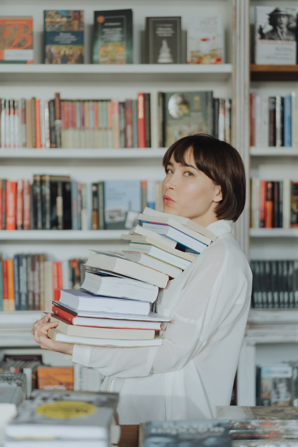 woman holding tall stack of books