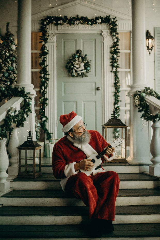 man in santa claus costume holding a ukulele in front of a decorated white house