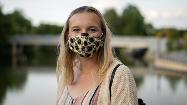 woman wearing sunflower dress and face mask
