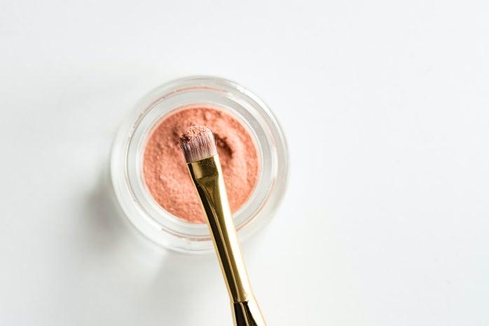 brown makeup brush in pink powder
