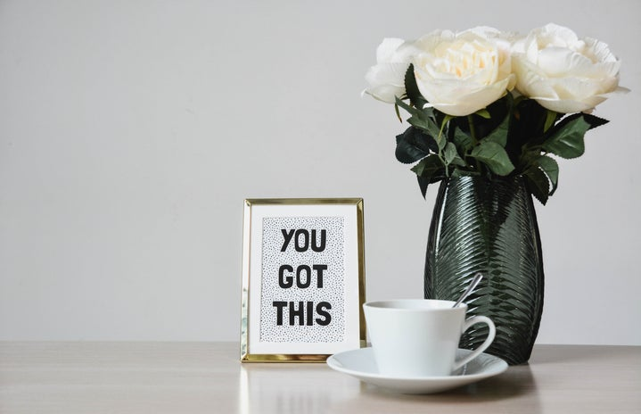 """White flowers in a vase. There is a sign stating \""""you got this\"""" to the left of the flowers and a teacup placed on top of a plate with a silverspoon placed inside."""