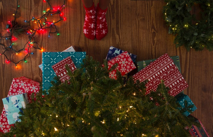 Top view of person wearing Christmas socks standing in front of Christmas tree surrounded by presents