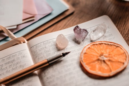 close up photo of a journal with a pen, some crystals, and an orange slice