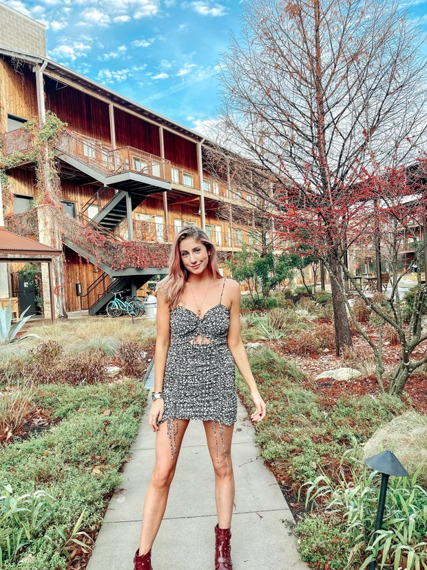 Girl in a dress stands in front of a building surrounded by greenery