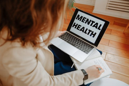"""laptop open with """"mental health"""" written on it while a woman writes in an open notebook"""