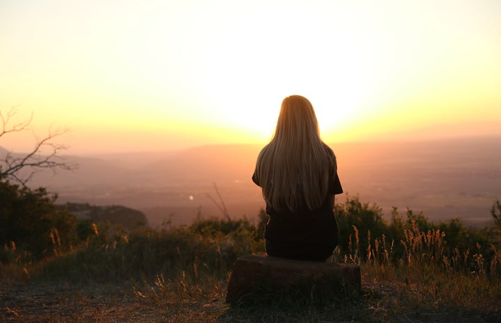 woman sitting on a rock looking at the sunset