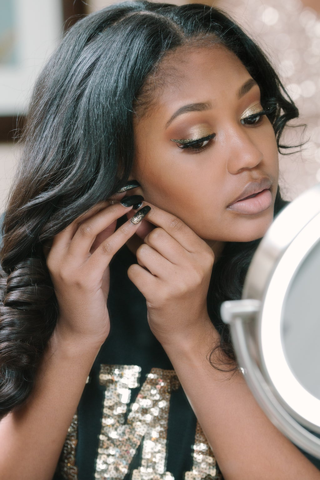Young woman with make up on putting on her earrings.