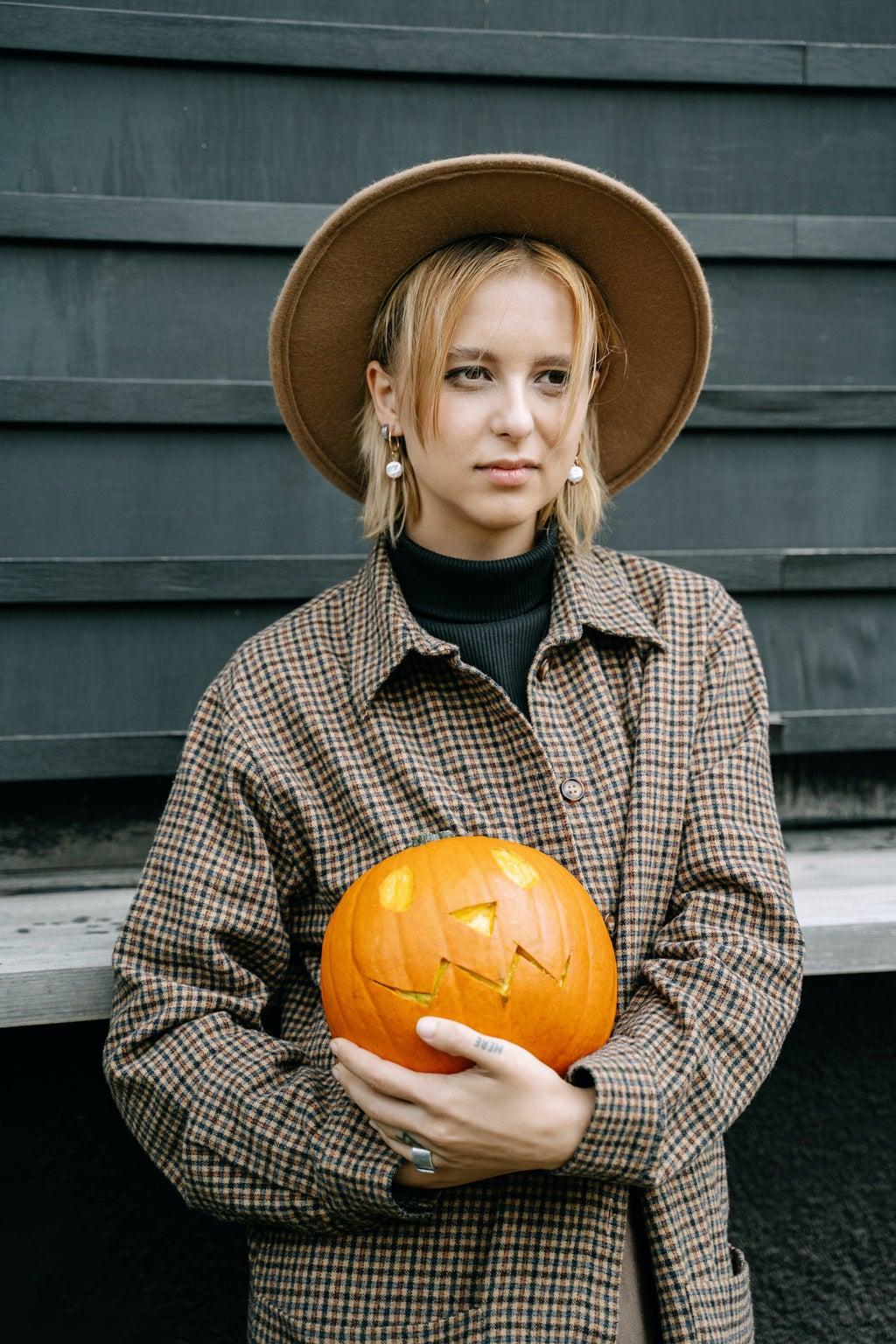 woman holding pumpkin and wearing fedora