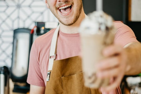 Man holding a smoothie and smiling.