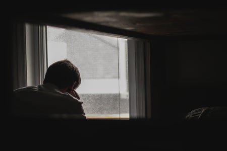 Person waiting by window, sad