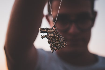 person holding up a silver Winter Coming Stark necklace