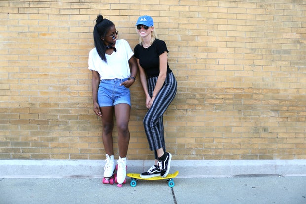 two girls friends baseball cap sunglasses skateboard roller skates happy