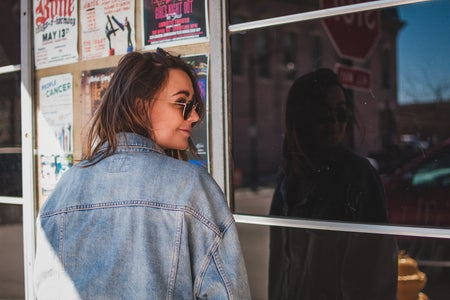 girl with jean jacket in front of shop