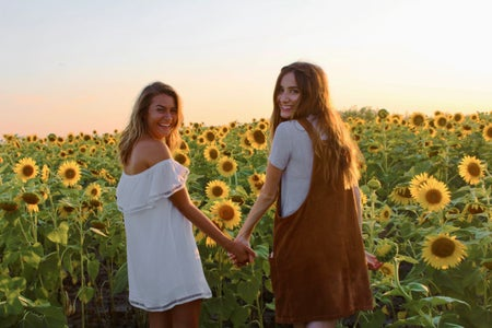 best friends holding hands sunflower field dresses summer happy sunset