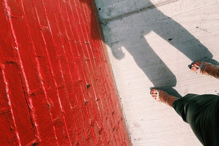 red wall shoes shadow brick street