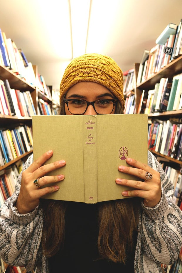The Lalagirl With Beanie Holding Book Up