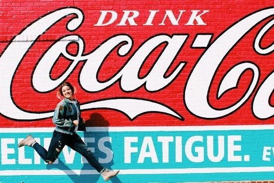 Amelia Kramer-Girl Jumping In Front Of Coca Cola Mural