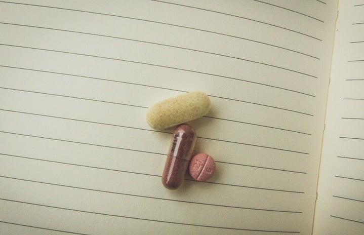Kristen Bryant-Close Up Pills On Notebook
