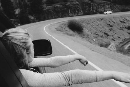 Anna Schultz-Girl On Road Trip Hands Out Window B&W