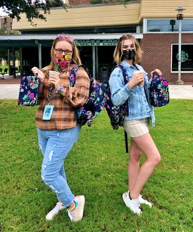 two students standing with coffee back to back