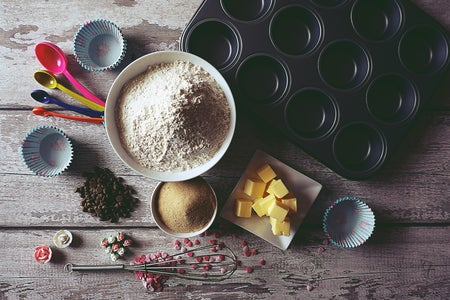 baking ingredients on a table next to a cupcake tray