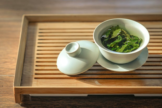 green tea leaves in white cup on wooden table