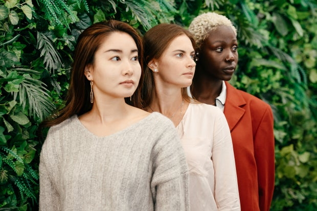 three women in front of a green hedge